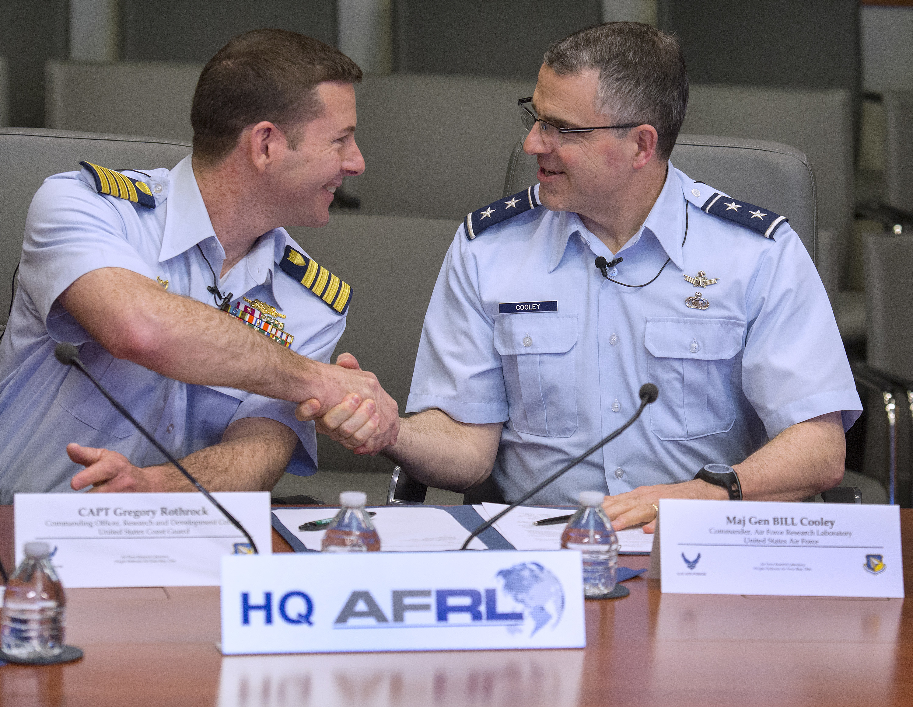 U.S. Coast Guard Capt. Greg Rothrock, Coast Guard Research and Development Center commanding officer, and Air Force Maj. General William Cooley, Air Force Research Laboratory commander, shake hands April 12, 2018, on Wright-Patterson Air Force Base, Ohio, after they signed a memorandum of understand between their two organizations. The agreement allows USCG RDC and AFRL to work together on tasks of mutual benefit. (U.S. Air Force photo by R.J. Oriez)